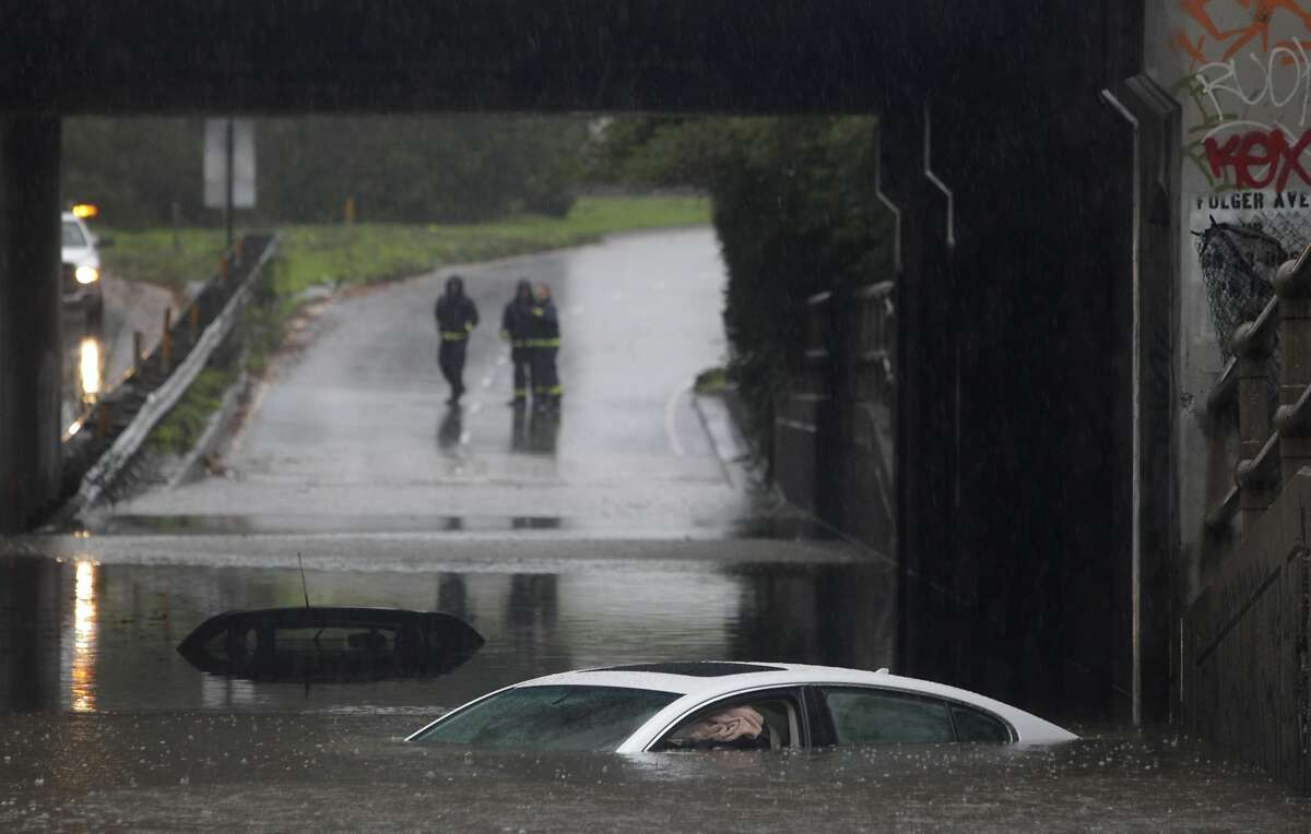 Berkeley firefighters stand on the on-ramp to eastbound I-80 beyond cars partially submerged in a flooded section of the Ashby Avenue underpass as a major storm hits the area in Berkeley, Calif. on Thursday, Dec. 11, 2014.