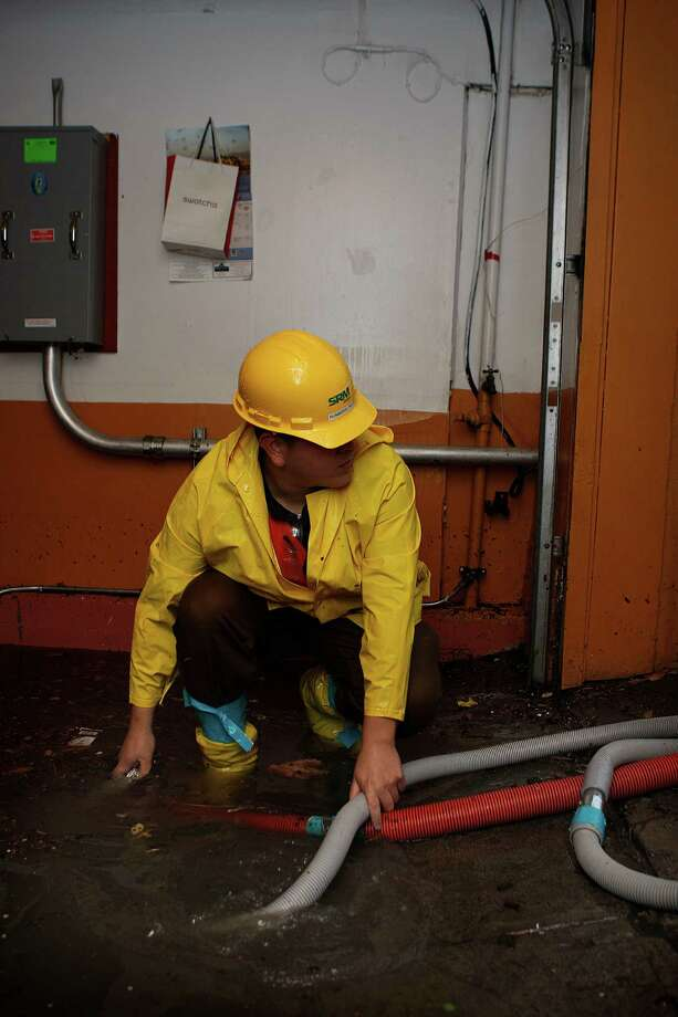 An employee from Service Master Recovery Management drains a basement flood at 2180 Folsom St. in San Francisco, on Thursday. Photo: Liz Hafalia / The Chronicle / ONLINE_YES