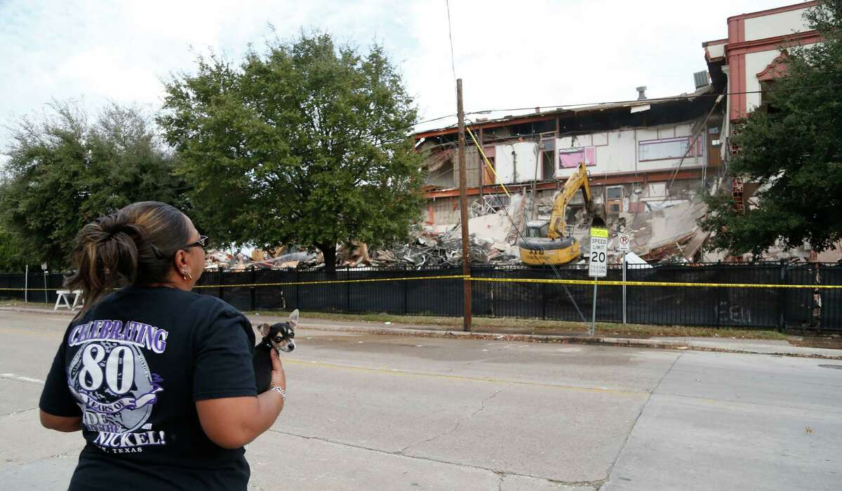 Kathy Blueford-Daniels watches as demolition crews start tearing down the old Phyllis Wheatley High School building, Thursday, Dec. 11, 2014, in Houston, over objections from some in the Fifth Ward community after a judge ruled Wednesday in HISD's favor.