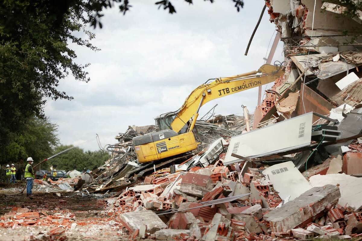 Demolition crews start tearing down the old Phyllis Wheatley High School building, Thursday, Dec. 11, 2014, in Houston, over objections from some in the Fifth Ward community after a judge ruled Wednesday in HISD's favor.