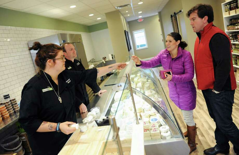 Cheesemongers Camille Royce and Kevin Palmaccio give a sample to Germaine and Charlie Andruss, of Cos Cob, at the Greenwich Cheese Company at 154 Putnam Ave. in the Cos Cob section of Greenwich, Conn. Thursday, Dec. 11, 2014.  Building off the success of the popular Fairfield Cheese Company, co-owners Laura Downey and Chris Palumbo brought a new location to Greenwich that will carry a selection of cut-to-order cheese, artisanal and farmstand cheese from around the world and an array of handmade charuterie and specialty food accompaniments. Photo: Tyler Sizemore / Greenwich Time