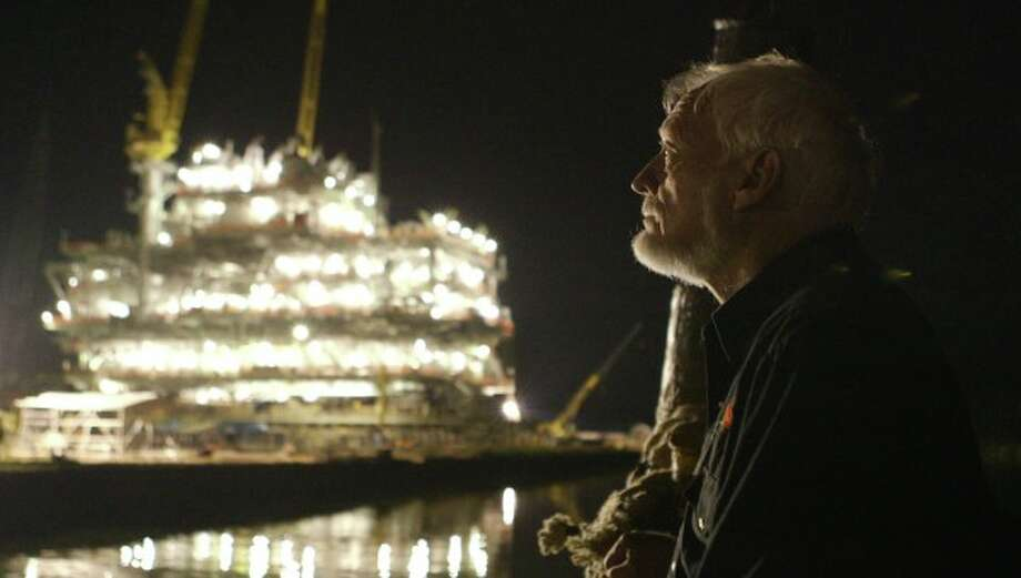 "Latham Smith looks out at an oil rig at night in ""The Great Invisible,"" a documentary on the Deepwater Horizon oil-rig explosion as seen through the eyes of oil executives, survivors and Gulf Coast residents who experienced it first hand. Photo: Radius-TWC / ONLINE_YES"