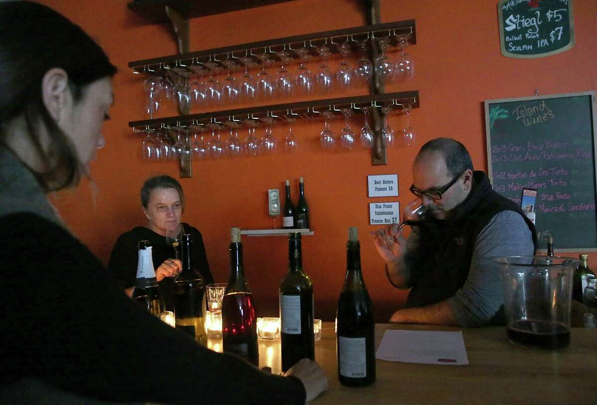 Elane Wood (left), Vicki Skugrud and Steven Sherman know how to make the most of rainy weather - wine tasting by candlelight in San Francisco