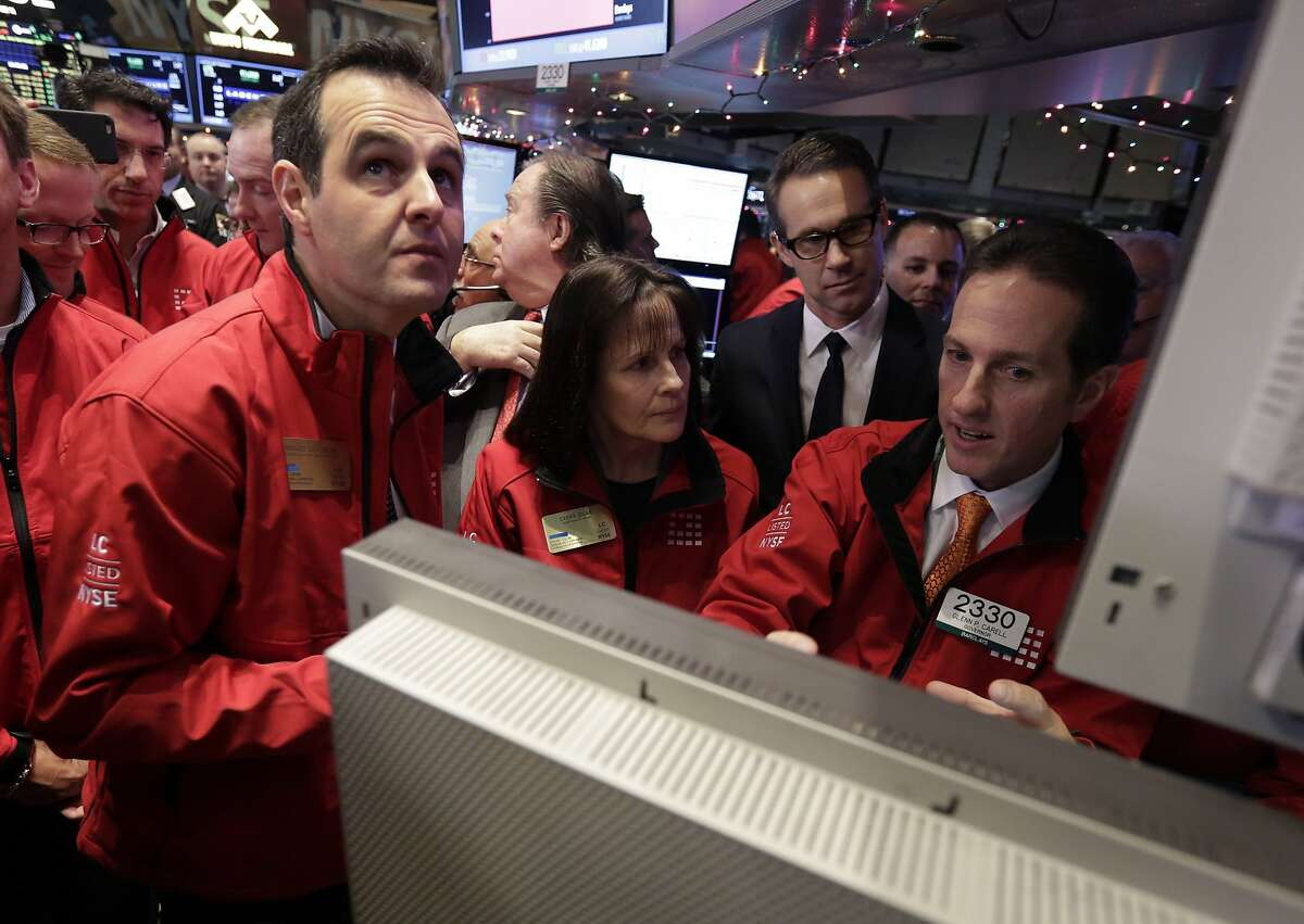 Renaud Laplanche, left, Founder & CEO of Lending Club, and CFO Carrie Dolan, huddle with specialist Glenn Carell as they wait for their company's IPO to begin trading, on the floor of the New York Stock Exchange, Thursday, Dec. 11, 2014. Lending Club, a peer-to-peer lending platform, rose $8.56, or 57 percent, to $23.66 on its first day of trading. (AP Photo/Richard Drew)