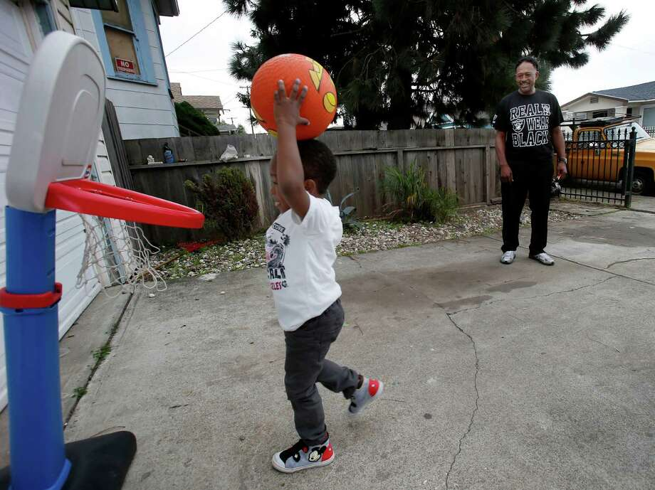Ron Amey (right) watches as his grandson Niko goes in to dunk the ball Sunday Dec. 7, 2014. The Amey family in Oakland got help with finances from Season of Sharing while the father, Ron, recovers from cancer. Photo: Brant Ward / The Chronicle / ONLINE_YES