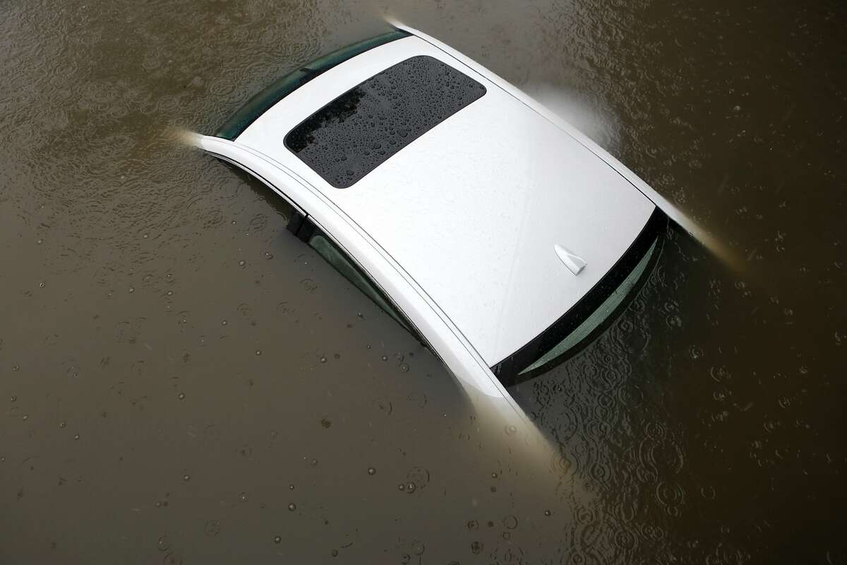 Flood waters rise over the top of a car on Ashby Avenue in Berkeley, just east of Highway 580, during a severe storm on Thursday, December 11, 2014.