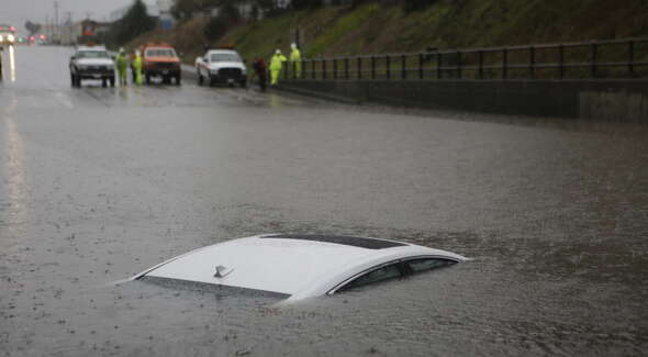 CalTrans workers watch as flood waters rise over the top of a car on Ashby Avenue in Berkeley, just east of Highway 580, during a severe storm on Thursday, December 11, 2014.