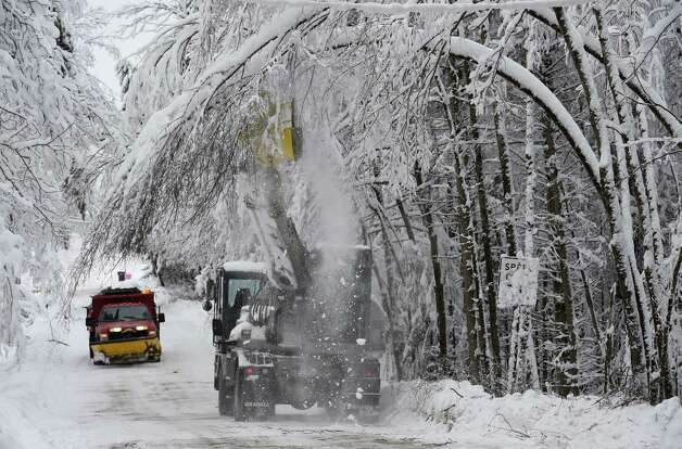 Duanesburg equipment operator Stephen Ash uses a Gradall axe head devise to trim low hanging branches due to the heavy snow load Thursday afternoon on Turnbull Road Dec. 11, 2014 in Duanesburg, N.Y.    (Skip Dickstein/Times Union) Photo: SKIP DICKSTEIN