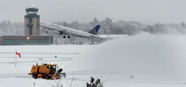 A commercial aircraft takes off from the Albany International Airport as grounds crews with high powered snow blowers remove snow after a three day storm dropped almost a foot of snow on the airport Dec. 11, 2014 in Colonie, N.Y.   (Skip Dickstein/Times Union) Photo: SKIP DICKSTEIN