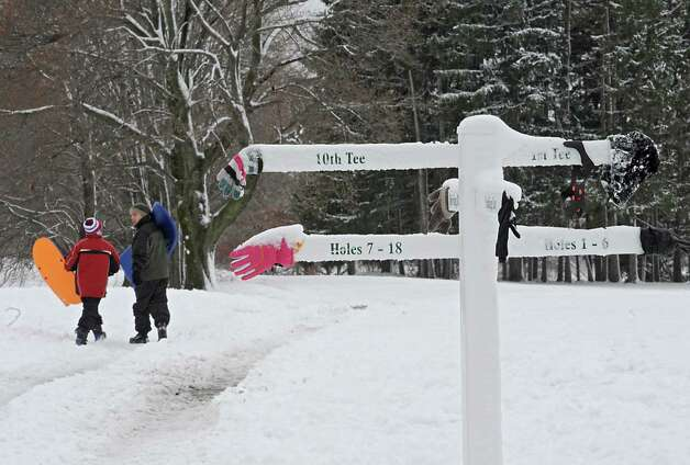 Logan Dittmer, 12, of Albany and his brother Ian, 24, right, walk to a hill to enjoy some sledding at Capital Hills at Albany on Thursday, Dec. 11, 2014 in Albany, N.Y. (Lori Van Buren / Times Union) Photo: Lori Van Buren