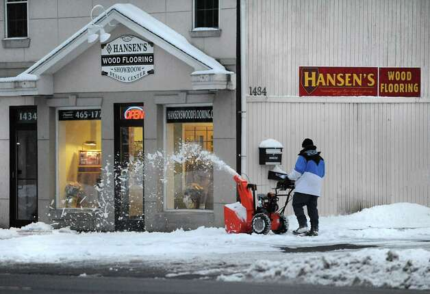 A person snowplows the walkway in front of Hansen's Wood Flooring on Thursday, Dec. 11, 2014 in McKownville, N.Y. (Lori Van Buren / Times Union) Photo: Lori Van Buren