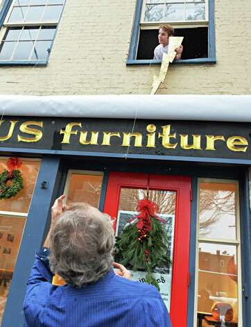 Long-time Troy artist and furniture craftsman Jim Lewis calls to Zeus above (played by his studio assistant Tom Roland) to change the name of his shop from Icarus to Springwood Studios during a ceremony Thursday Dec. 11, 2014, in Troy, NY.  (John Carl D'Annibale / Times Union) Photo: John Carl D'Annibale / 00029818A