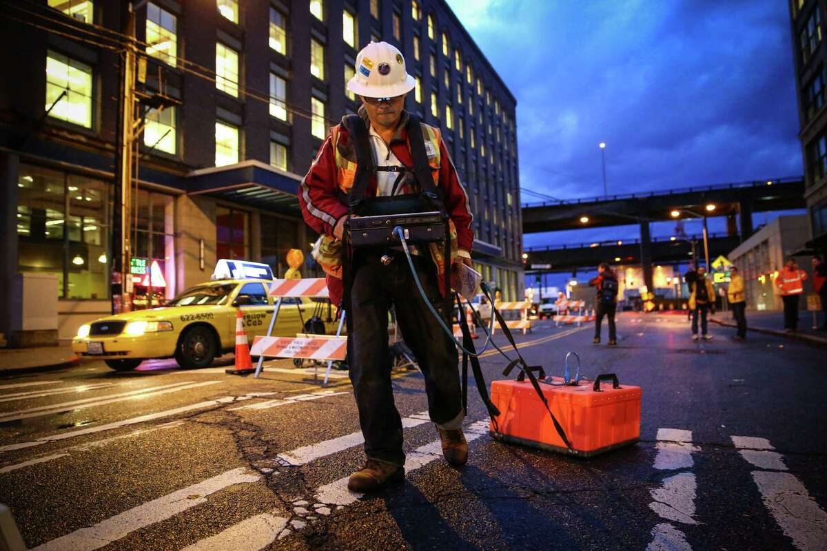 John Lui uses a ground-penetrating radar after an area of cracking and sinking were discovered on South King Street, adjacent to the Alaskan Way Viaduct and an area where a pit is being dug to rescue the broken waterfront tunnel boring machine. It was not determined if the sinking was related to the digging nearby. Photographed on Thursday, December 11, 2014.