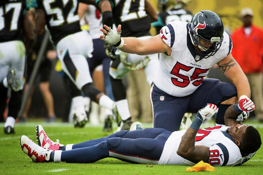Texans center Chris Myers motions for help from the trainers after wide receiver Andre Johnson was injured against the Jaguars. Photo: Smiley N. Pool, Staff / © 2014  Houston Chronicle
