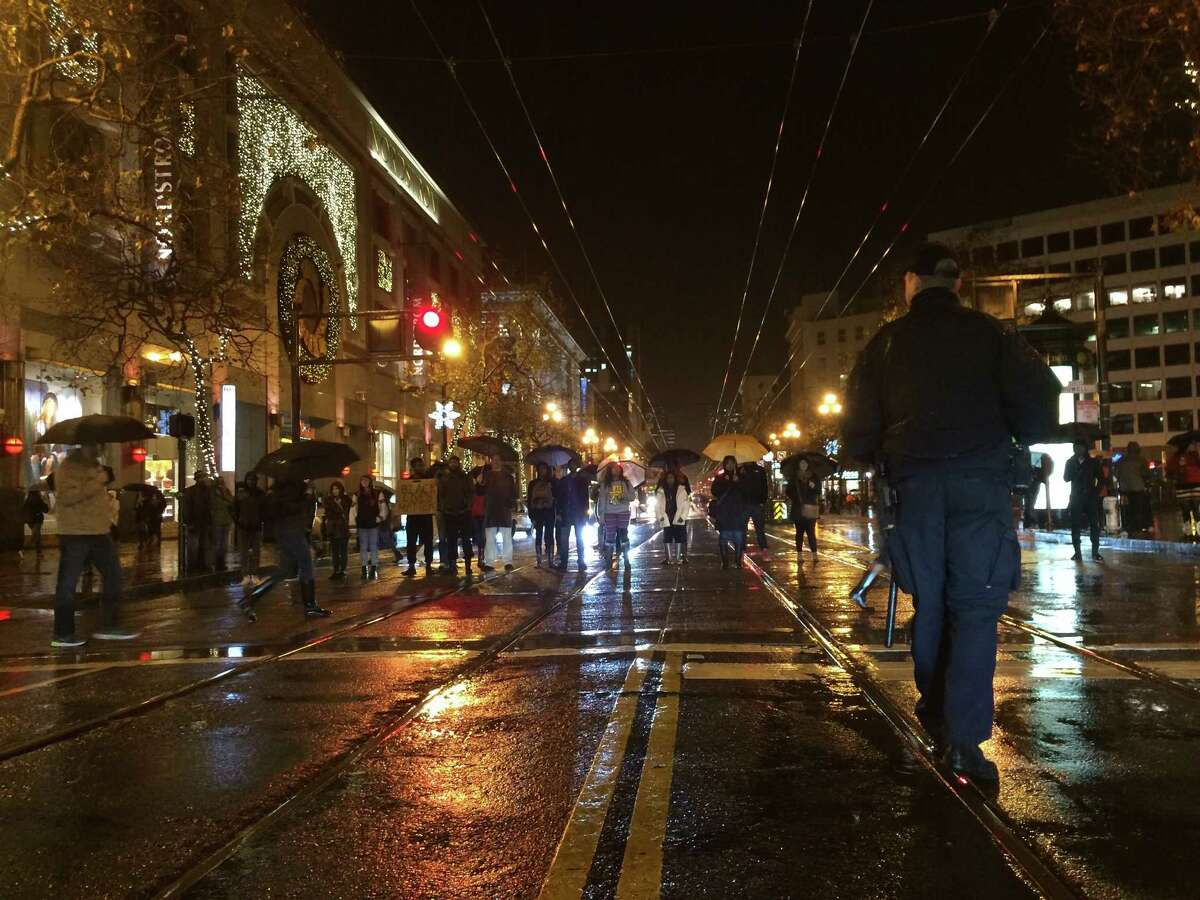 A group of about 20 protesters decrying racial injustice and police brutality blocks traffic on Market Street on Thursday.