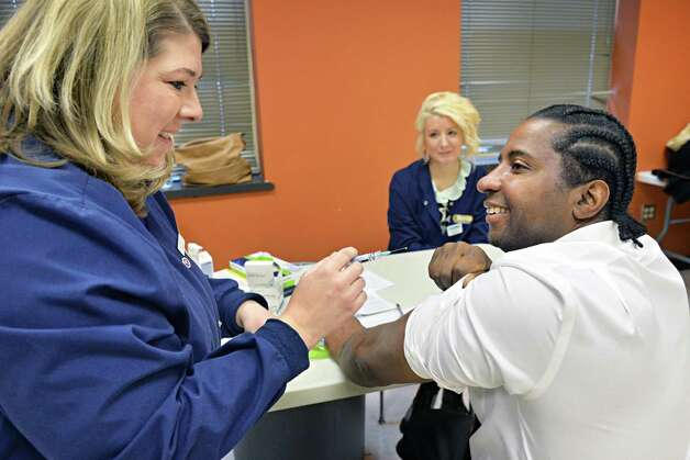 Pharmacist Jessica Marchese, left, of Marra's Pharmacy in Cohoes administers a flu shot to Albany City councilman Mark Robinson during a flu shot clinic at the Arbor Hill Community Center Thursday Dec. 11, 2014, in Albanuy, NY.   (John Carl D'Annibale / Times Union) Photo: John Carl D'Annibale / 00029791A