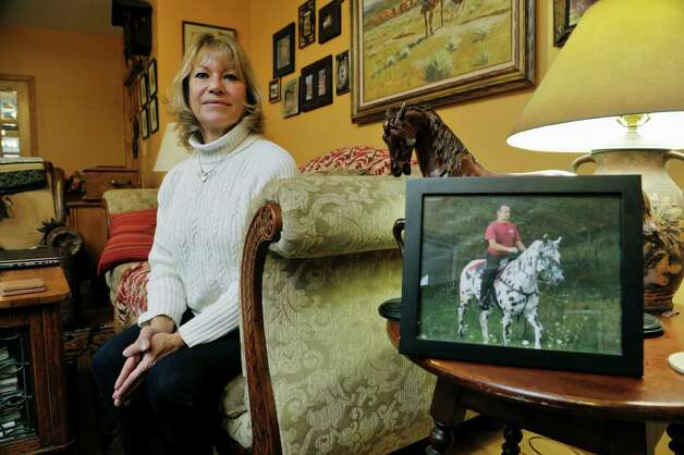 Dolores Meissner poses with a photograph of her late husband, Keith, at her home on Tuesday, Dec. 9, 2014, in Averill Park, N.Y.  Keith died about a year ago while rescuing horses from a barn fire.  In the photograph Keith is riding his horse, Midnight, which also died in the fire.  (Paul Buckowski / Times Union) Photo: Paul Buckowski / 00029751A