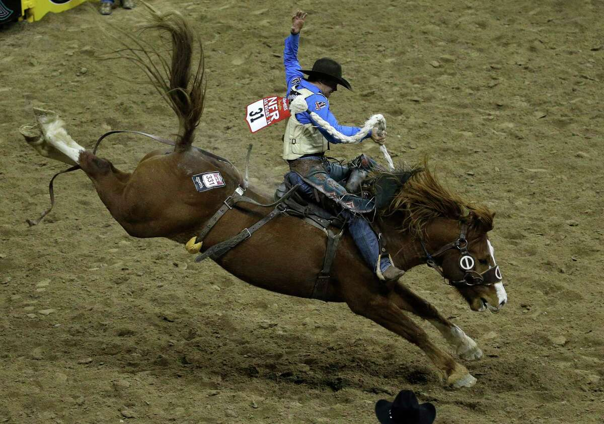 Saddle bronc rider Heath DeMoss from Heflin, La., rides for a first place score of 84.0 during the eighth go-round of the National Finals Rodeo Thursday, Dec. 11, 2014, in Las Vegas.
