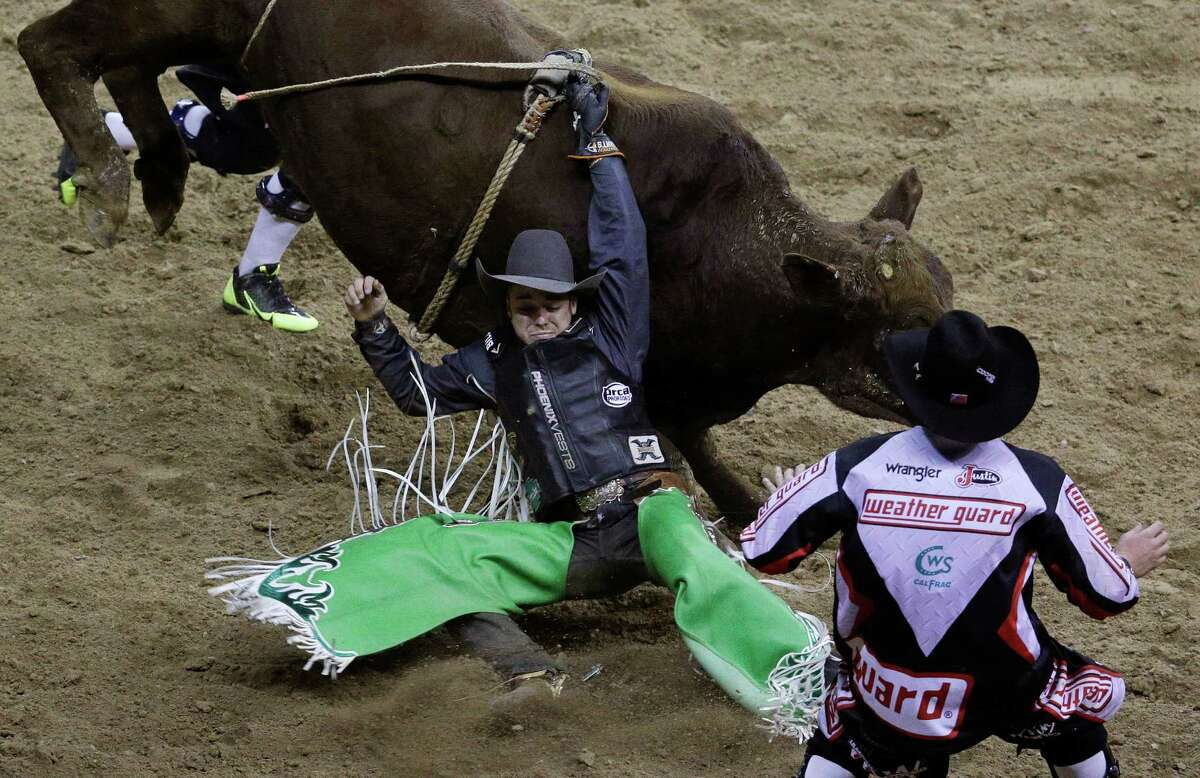 Bull rider Aaron Pass from Dallas, gets hung up on his bull during the eighth go-round of the National Finals Rodeo Thursday, Dec. 11, 2014, in Las Vegas.