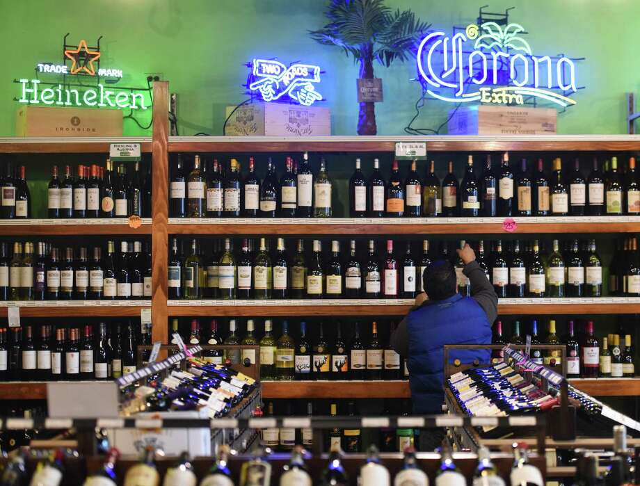Juan Ramirez restocks the shelves at Greenwich Wine and Spirits in the Riverside area of Greenwich, Conn. Thursday, Dec. 11, 2014.  There are more and more wine and spirits shops popping up in the Greenwich area and the town ranks ninth in Fairfield County with 3.4 liquor stores per 10,000 residents. Photo: Tyler Sizemore / Greenwich Time