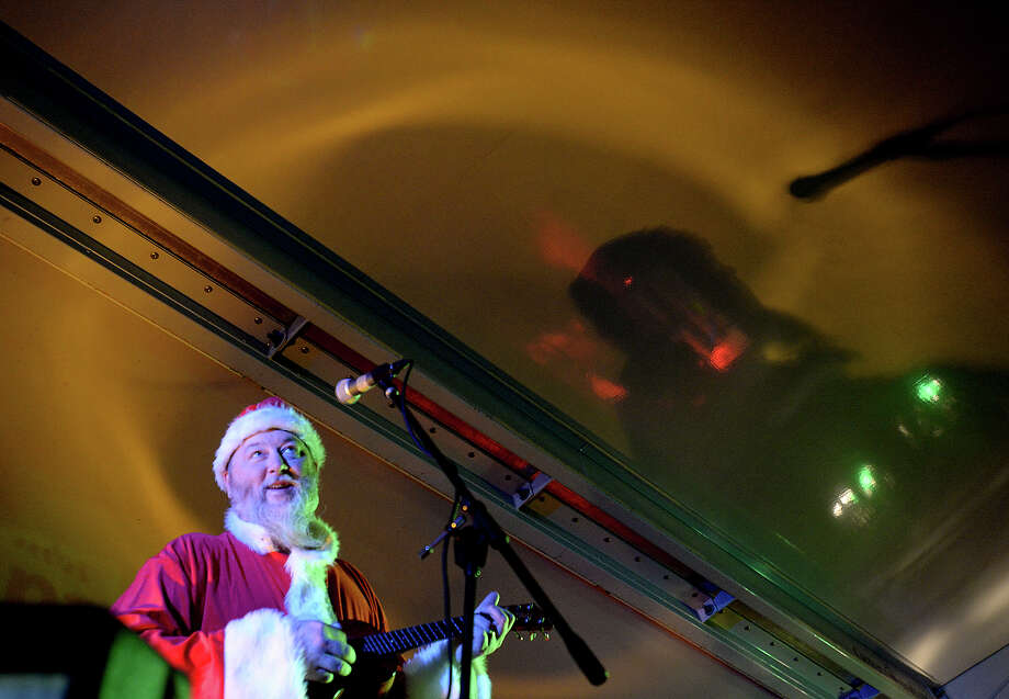 Kevin Russell gets in the spirit, donning a Santa suit, for his band Shiny Ribs' performance Thursday night at the Tunes for Toys show. A toy donation was the price of entry for dinner, drinks and entertainment, including featured act Shiny Ribs, at the event held at Eastex Automotive. The wagonful of collected toys will be donated to CASA, who will distribute them to the children involved in the program this holiday season. Photo taken Thursday, December 11, 2014 Kim Brent/The Enterprise Photo: Kim Brent / Beaumont Enterprise