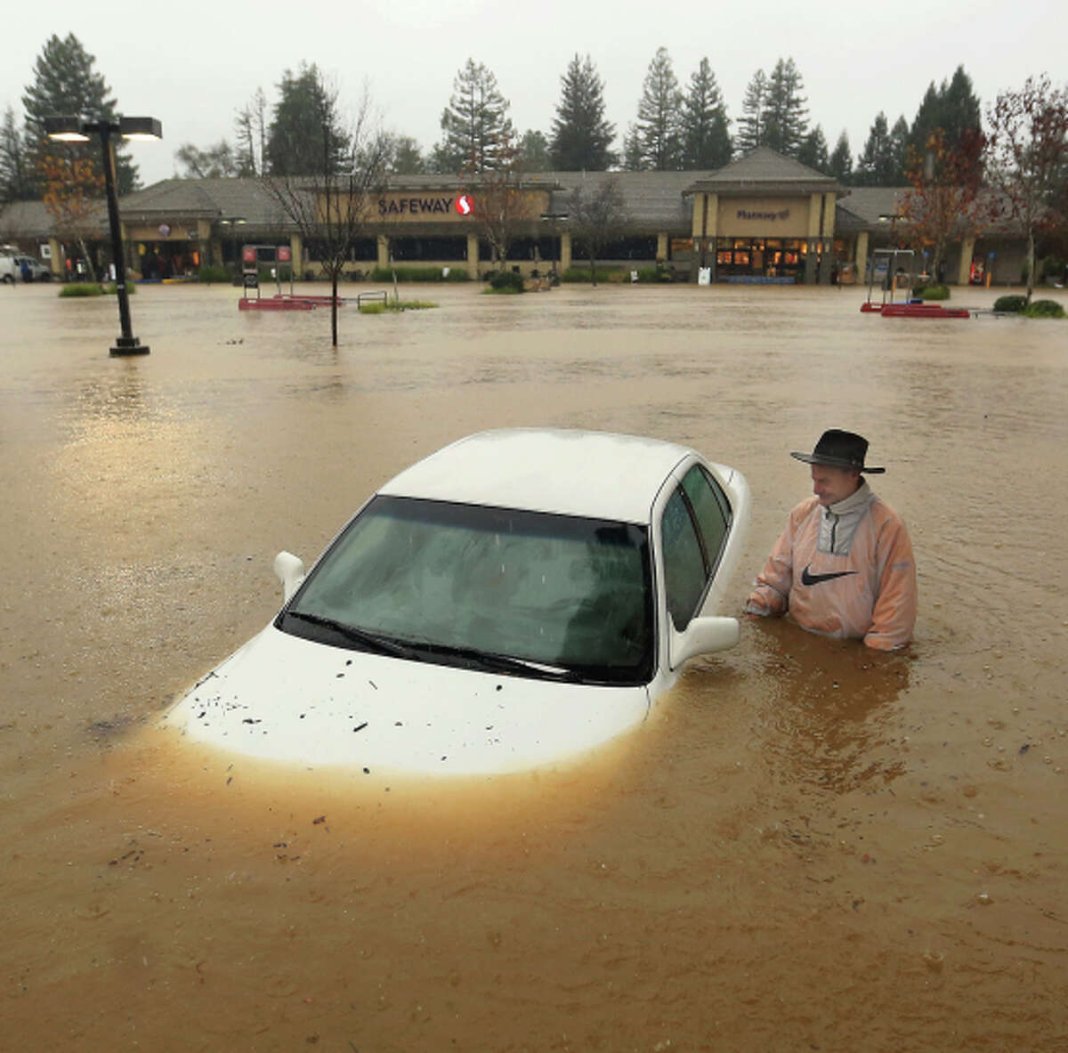 WHEN SAFEWAY SAYS NO OVERNIGHT PARKING, THEY MEAN IT: A Guerneville resident finds his car sitting window-deep in floodwater after leaving it overnight in the Safeway parking lot in Healdsburg, Calif.