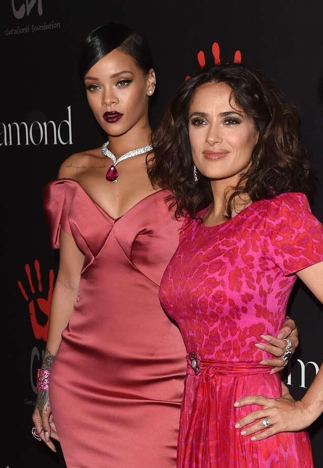 Recording artist Rihanna (L) and actress Salma Hayek attend Rihanna's First Annual Diamond Ball at The Vineyard on December 11, 2014 in Beverly Hills, California. Photo: Jason Merritt, Getty Images