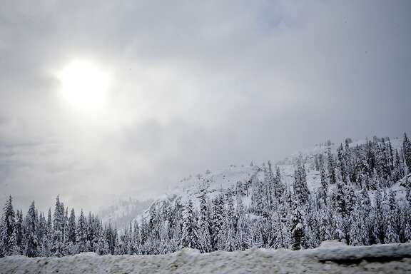 The sun breaks through the clouds near Donner Lake, Calif., on Friday Dec. 12, 2014, as the storm that covered the Bay Area with heavy rains yesterday left a blanket of snow across the Sierra Nevada mountains