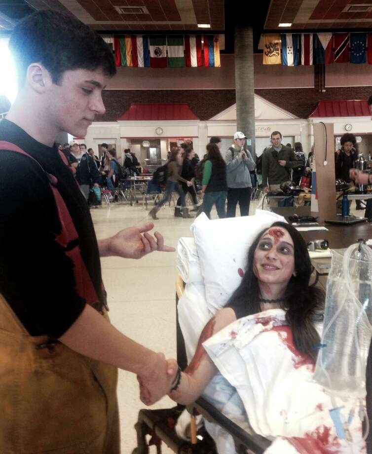 Greenwich High School seniors Nicholas Cesarini and Alexis Pollack, both fire explorers, at the Be Safe Day at the high school in Greenwich, Conn. on Friday, Dec. 12, 2014. Pollack portrayed a car accident victim at the event aimed to raise awareness about the work of the emergency services.   . Photo: Paul Schott / Greenwich Time