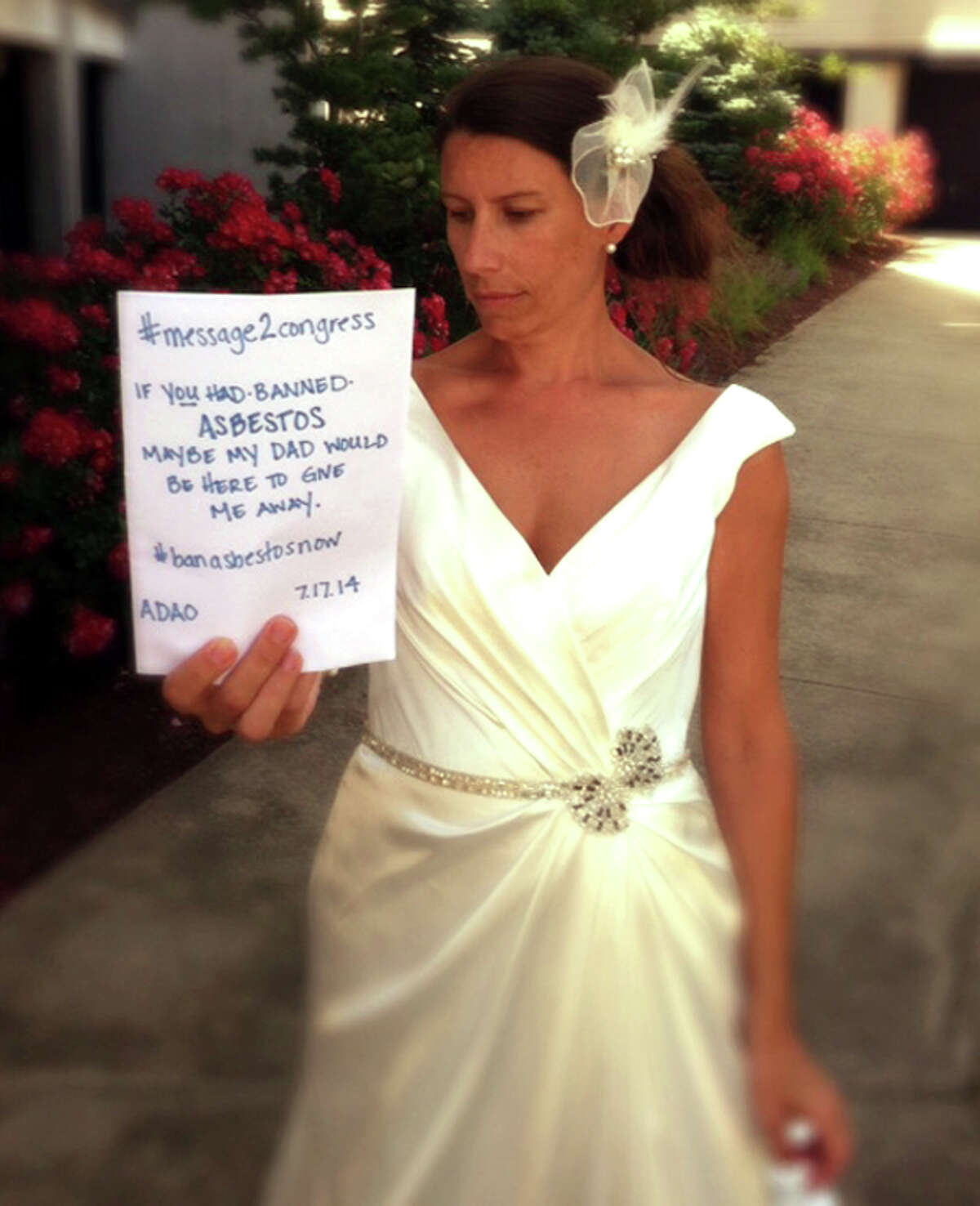 """When Courtney Davis got married last summer, she posed in her gown with a large placard: """"Message2Congress: If you had banned asbestos, maybe my dad would have been here to give me away."""" Davis' father, Larry W. Davis of Southington, Conn., died in July 2012 of mesothelioma, a cancer of the lining of the chest that is 100 percent preventable because is caused by exposure to asbestos fibers."""