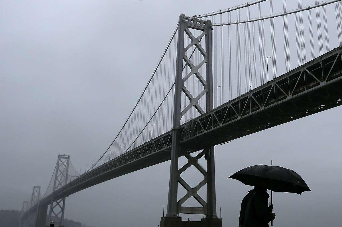 FILE PHOTO: A pedestrian walks in the rain next to the San Francisco-Oakland Bay Bridge on December 11, 2014 in San Francisco, California.