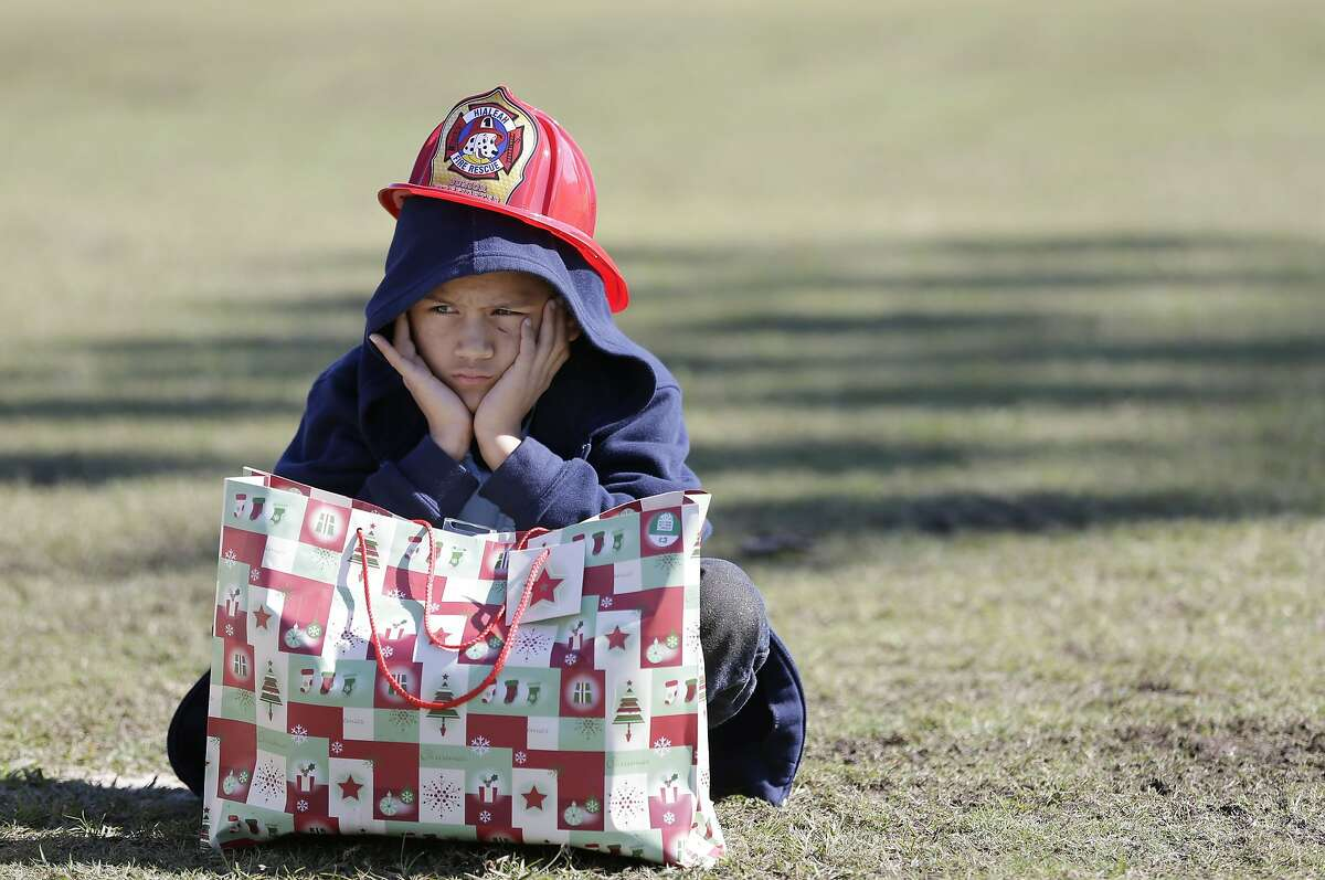 WAS HOPING FOR A BIKE: Nine-year-old Elvin Perez-Rios sits alone with his gift from Santa in Hialeah, Fla. About 400 underprivileged children were treated to lunch, presents, a visit from Santa and Mrs. Claus, and demonstrations from the Hialeah police department's K-9 Unit, SWAT team and the Hialeah fire department.