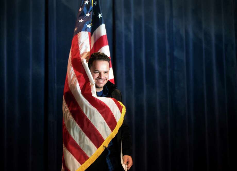 Eder Souza, of Bridgeport, originally from Brazil, pulls the American flag around him as he poses for a picture with his certificate of citizenship Friday, Dec. 12, 2014, during a naturalization ceremony for new American citizens at the Klein Auditorium in Bridgeport, Conn. Photo: Autumn Driscoll / Connecticut Post