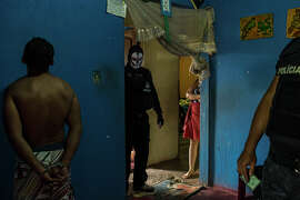 A masked police officer searches rooms during a drug raid in a shantytown on the outskirts of Manaus. The city is a reeling from turf wars between rival gangs, targeted killings of police officers and grisly murders.