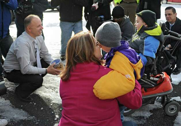 Frank Squeo, founder of Baking Memories 4Kids, left, presents Caleb Cunniff, 7, in wheelchair, and his family with an all-expenses-paid trip to Florida on Friday, Dec. 12, 2014 in Rotterdam, N.Y. Trooper David Cunniff died  while on duty almost a year ago. Caleb's mother, Amy, hugs his brother Zachary, 6, in foreground. (Lori Van Buren / Times Union) Photo: Lori Van Buren / 00029838A