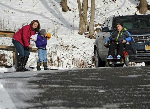 Amy Cunniff and her two sons, Zachary, 6, and Caleb, 7, right, look on as trucks from the Pine Grove Fire Department show up to their home on Friday, Dec. 12, 2014 in Rotterdam, N.Y. Caleb Cunniff and his family were presented a trip to Florida. Trooper David Cunniff died  while on duty almost a year ago.  (Lori Van Buren / Times Union) Photo: Lori Van Buren / 00029838A