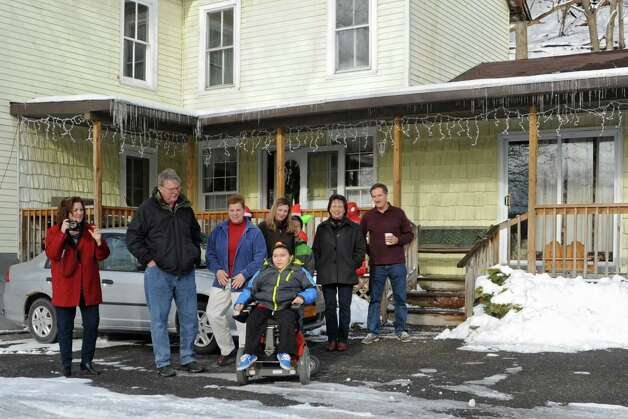 Caleb Cunniff, 7, in wheelchair, along with family and friends look on as trucks from the Pine Grove Fire Department show up to their home on Friday, Dec. 12, 2014 in Rotterdam, N.Y. Caleb Cunniff and his family were presented a trip to Florida. Trooper David Cunniff died  while on duty almost a year ago.  (Lori Van Buren / Times Union) Photo: Lori Van Buren / 00029838A