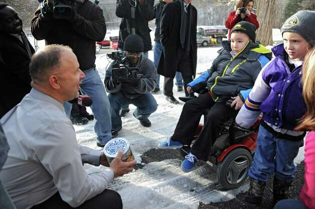Frank Squeo, founder of Baking Memories 4Kids, left, presents Caleb Cunniff, 7, in wheelchair, and his family with an all-expenses-paid trip to Florida on Friday, Dec. 12, 2014 in Rotterdam, N.Y. Trooper David Cunniff died  while on duty almost a year ago. Caleb's brother Zachary, 6, stands at right. (Lori Van Buren / Times Union) Photo: Lori Van Buren / 00029838A