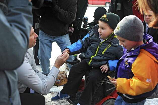 Frank Squeo, founder of Baking Memories 4Kids, left, offers cookies as he presents Caleb Cunniff, 7, in wheelchair, and his family with an all-expenses-paid trip to Florida on Friday, Dec. 12, 2014 in Rotterdam, N.Y. Trooper David Cunniff died almost a year ago  while on duty. Caleb's brother Zachary, 6,  stands to the right. (Lori Van Buren / Times Union) Photo: Lori Van Buren / 00029838A