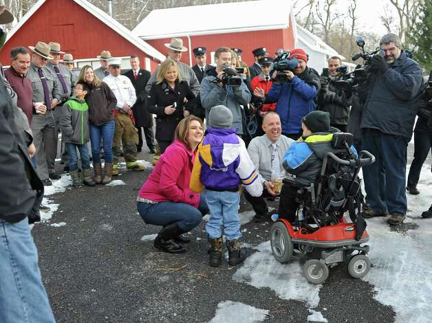 Frank Squeo, founder of Baking Memories 4Kids, center, offers cookies as he presents Caleb Cunniff, in wheelchair, and his family with an all-expenses-paid trip to Florida on Friday, Dec. 12, 2014 in Rotterdam, N.Y. Trooper David Cunniff died almost a year ago  while on duty. Caleb's brother Zachary, 6, and his mom, Amy, are seen next to him on left. (Lori Van Buren / Times Union) Photo: Lori Van Buren / 00029838A