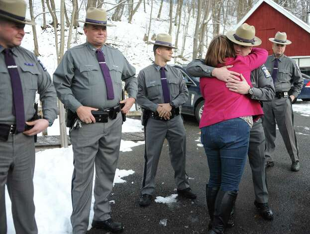 Amy Cunniff hugs her trooper family as her family is presented with a trip to Florida on Friday, Dec. 12, 2014 in Rotterdam, N.Y. Trooper David Cunniff died almost a year ago while on duty.  (Lori Van Buren / Times Union) Photo: Lori Van Buren / 00029838A