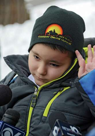 Caleb Cunniff, 7, wears a hat with his father's name on it as he is interviewed after he and his family were presented with a trip to Florida from Frank Squeo, founder of Baking Memories 4Kids, on Friday, Dec. 12, 2014 in Rotterdam, N.Y. His father Trooper David Cunniff died almost a year ago  while on duty. (Lori Van Buren / Times Union) Photo: Lori Van Buren / 00029838A