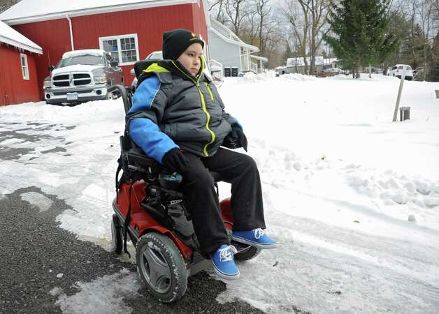 Caleb Cunniff, 7, maneuvers his wheelchair in his driveway after being presented with a trip to Florida for him and his family from Frank Squeo, founder of Baking Memories 4Kids, on Friday, Dec. 12, 2014 in Rotterdam, N.Y. His father Trooper David Cunniff died almost a year ago  while on duty. (Lori Van Buren / Times Union) Photo: Lori Van Buren / 00029838A