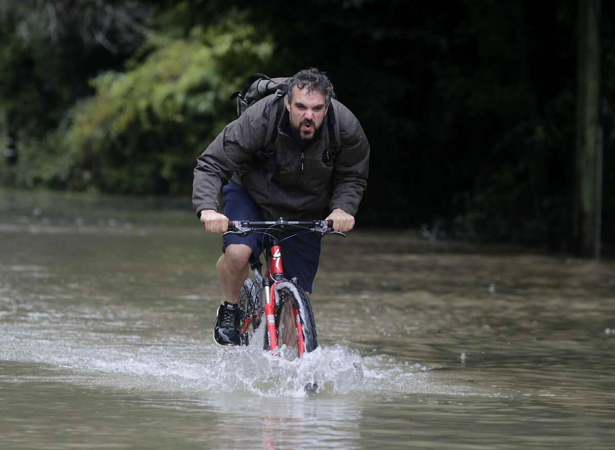 Corey Weaver pedals through flood waters as the Russian River surges in Guerneville, Calif. on Friday, Dec. 12, 2014.