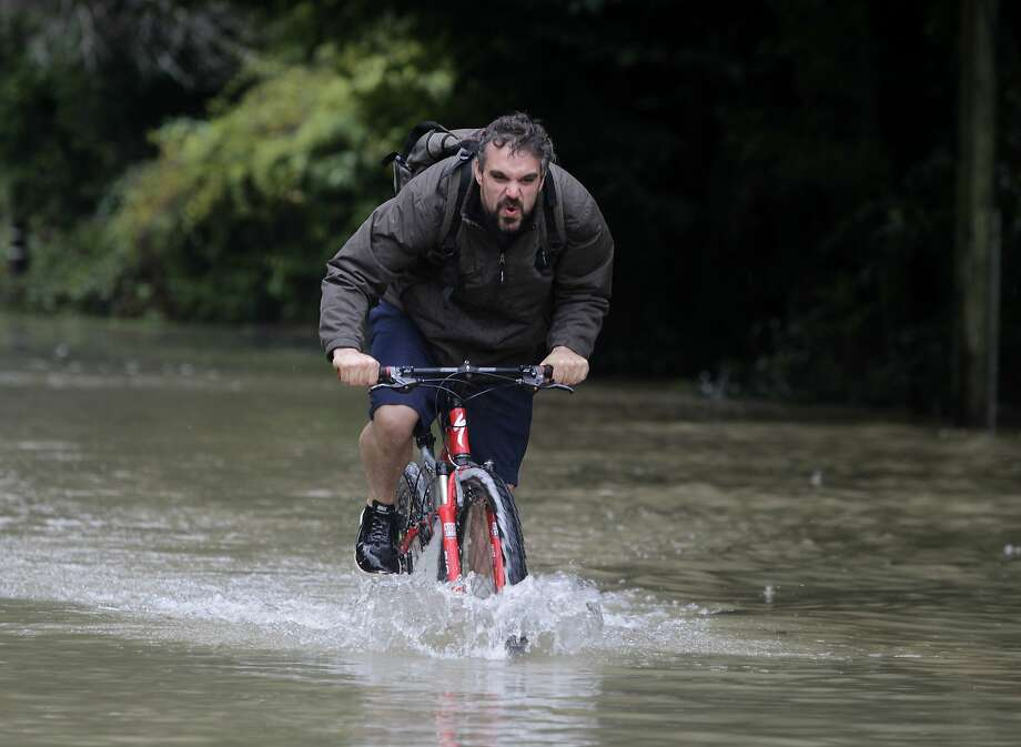 Corey Weaver pedals through flood waters as the Russian River surges in Guerneville, Calif. on Friday, Dec. 12, 2014. Photo: Paul Chinn, The Chronicle