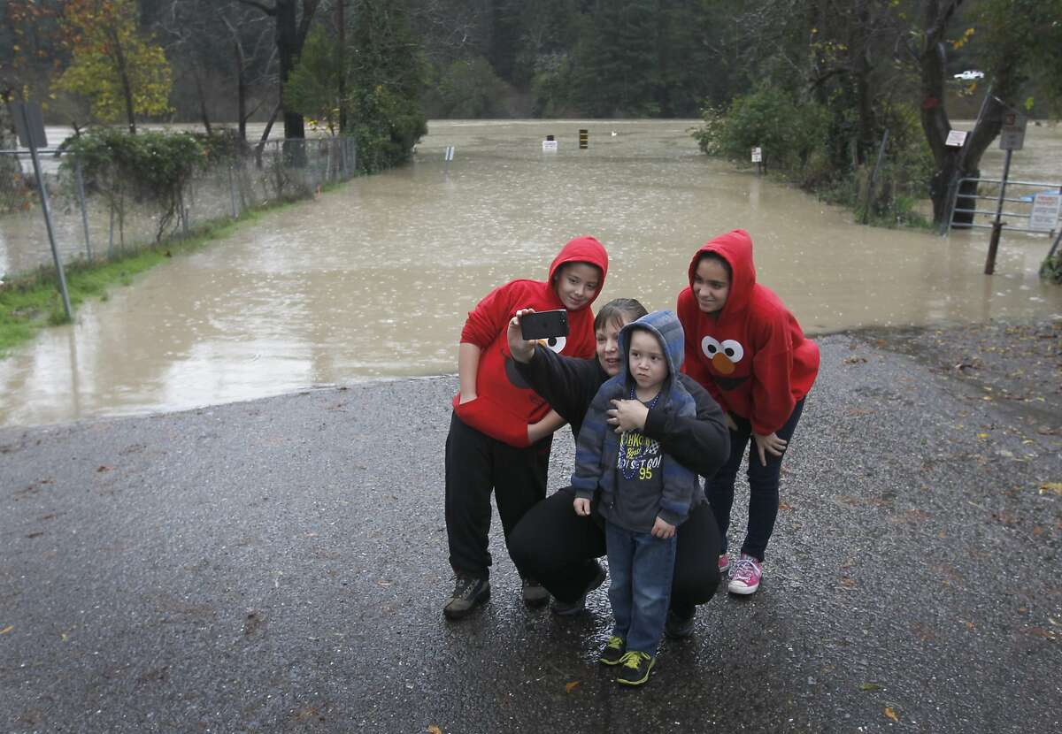 Danielle Williams takes a selfie with her children Cole, 9, Paris, 11, and Brody 4, as the Russian River floods at Johnson's Beach in Guerneville, Calif. on Friday, Dec. 12, 2014.