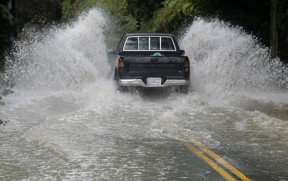 A pickup drives through a flooded section of Neeley Road as the Russian River flows over its bank in Guerneville, Calif. on Friday, Dec. 12, 2014. Photo: Paul Chinn, The Chronicle