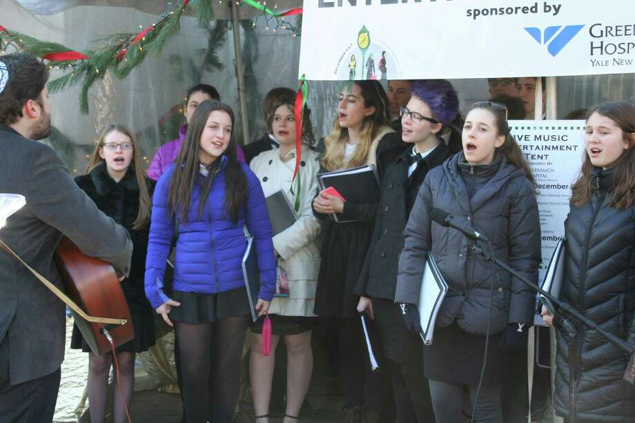 On Sunday, December 7, the Temple Sholom Teen Choir pitched in to provide music for the 2014 edition of the annual Greenwich Holiday Stroll. The choral group is led by Cantor Asa Fradkin of Temple Sholom and is comprised of 12 to 17 year olds. A small crowd of onlookers gathered on Greenwich Avenue to listen as the choir performed a selection of traditional Jewish songs as well as a special, Hawaiian rendition of ìSomewhere Over the Rainbow,î featuring two young ukulele players. From left, on guitar, Cantor Asa Fradkin of Temple Sholom and Teen Choir members; Melanie Leguizano, Talia Neuman, Suzie Katz Sam Schecter, Ashley Lilien, Ali Angelo and Olivia Dallape perform on Greenwich Avenue during Greenwich Holiday Stroll, 2014. Photo: Contributed Photo / Greenwich Time Contributed