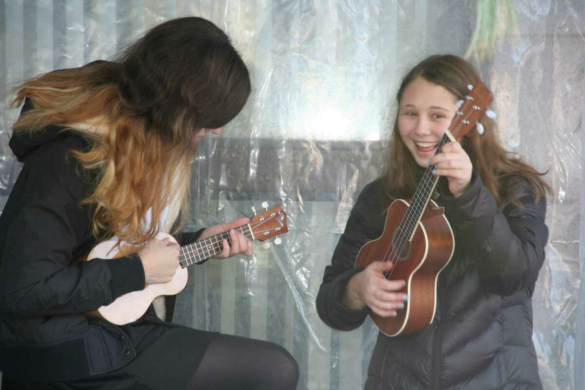 Sam Schecter and Olivia Dallape, of the Temple Sholom Teen Choir, tune their ukuleles prior to performing a Hawaiian rendition of