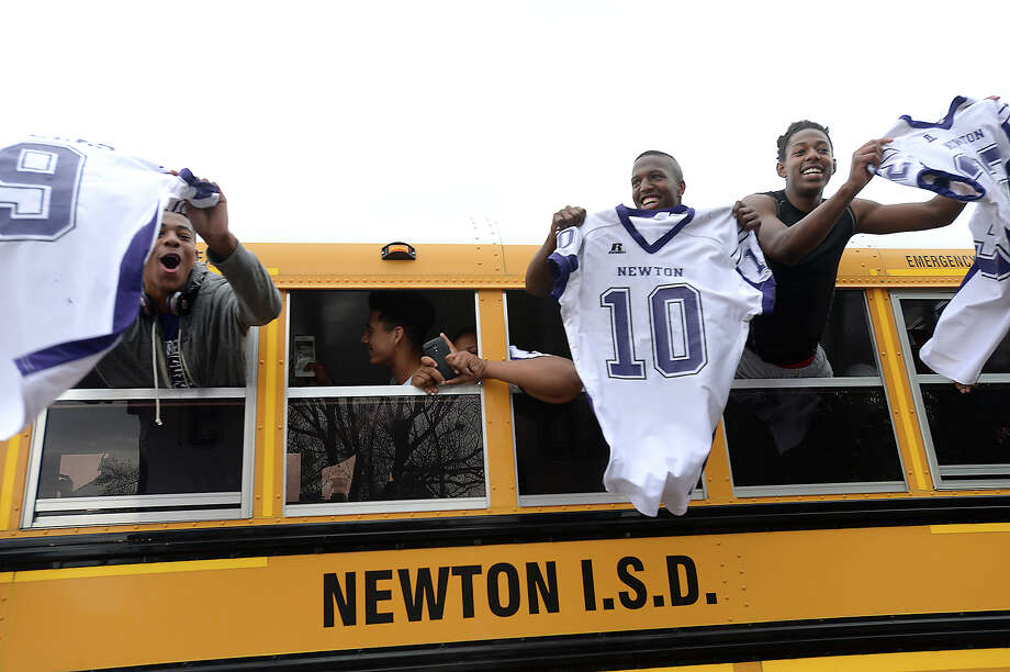 Newton football team members, including (from left) Gabe Foster, Raylin Davis, and Jace Thomas, wave to their fans, who filled the square downtown to cheer as their bus headed out to Waller for Friday's state semi-final football game against Blanco. Photo taken Thursday, December 11, 2014 Kim Brent/The Enterprise Photo: Kim Brent / Beaumont Enterprise
